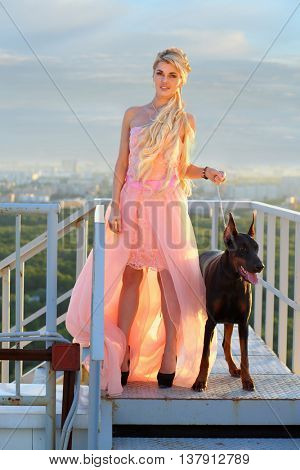 Beautiful girl with long blond hair in a pink dress with the Doberman on fire escape at the roof