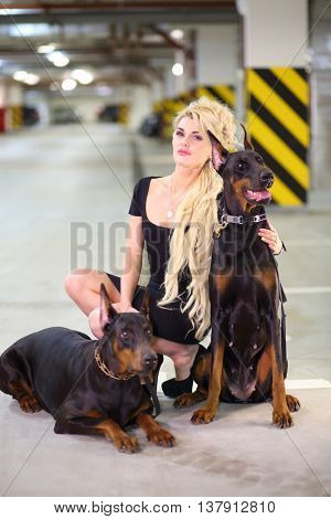 Blonde in a black dress crouched in an embrace with two Doberman in the underground parking