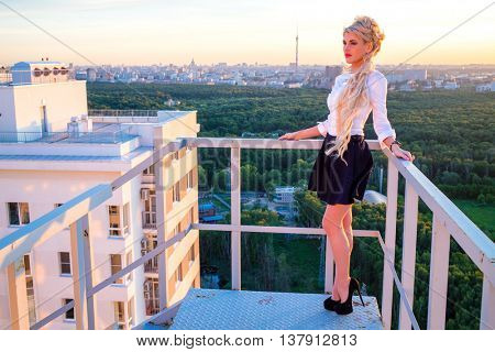 Beautiful blond with long hair in a white blouse and short skirt is standing on a fire escape on the roof
