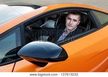 Happy young businessman driving luxury sport car