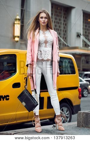 Full length portrait of beautiful fashion model girl holding black bag and standing on New York City street