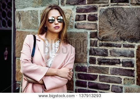 Beautiful fashion model woman wearing sunglasses and standing near brick wall