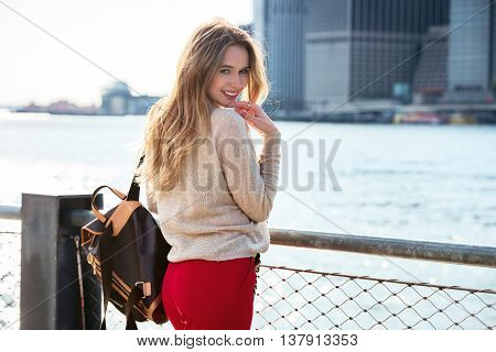 Cute young woman with beautiful smile posing near East River in New York City
