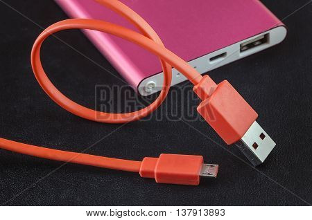 Orange color USB cable and red power bank on black leather background.