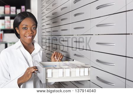 Black pharmacist at medicine cabinet choosing medicine
