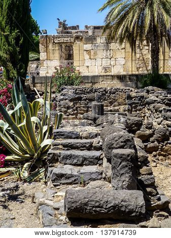 Archaeological site Capernaum ancient ruins of homes of black basalt and synagogue of white calcareous stone on the shore of the Sea of Galilee in Israel