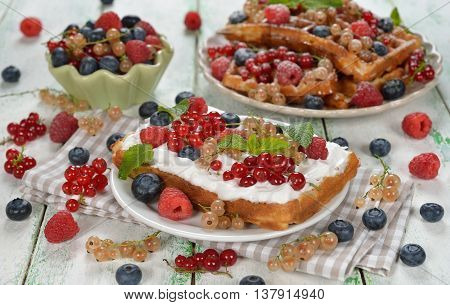 Waffles with whipped cream and berries on a white background