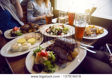 Friends having a dinner in the restaurant with salad barbeque and beer