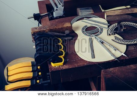 view on workplace with carved guitar shape with diffrerent instruments