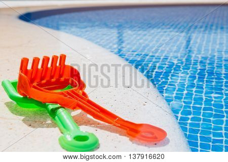 Close-up of kids plastic spade and rake on pool border in sunlight. Copy space available