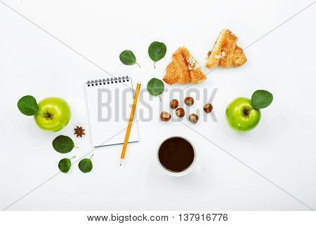 Cup of black coffee sketchbook with pencil green apple with leaves croissant and hazelnuts. Flat lay top view