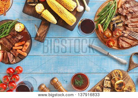 Grilled beef steak with grilled vegetables on a blue wooden table with copy space. Top view. Outdoors Food Concept