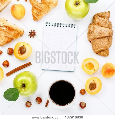 sketchbook with different ingredients for a healthy breakfast. sketchbook with cup of black coffee croissants green apples with leaves hazelnuts and apricots. Flat lay top view