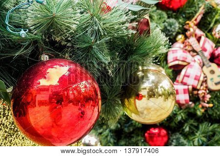 Christmas decorative spheres or baubles hanging on an artificial Christmas tree. A closeup view. The tungsten lighting gives the image a warm feeling.