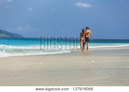 Young couple walking on a perfect tropical sandy beach