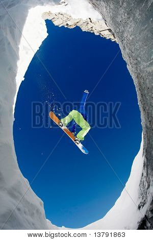 Below view of extreme snowboarder surrounded by rocky mounts covered with snow