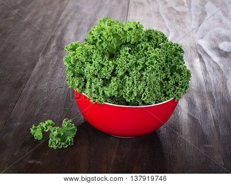 fresh green kale leaves in red ceramic bowl on vintage wooden table