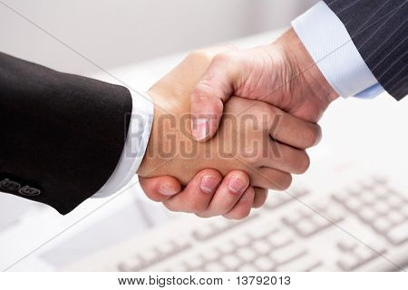 Close-up of business partners sharing hands over keyboard