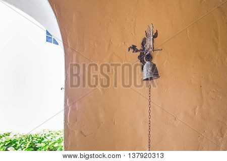 Exotic antique door bell in a stucco portico.