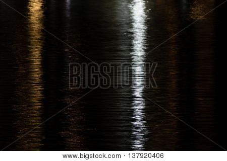 Reflection of yellow and white city lights shimmering on water in yellow and silver at night. Short shutter speed produced highlights against a mostly black background.