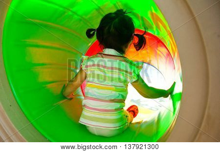 Kid playing in a playground sliding into a tunnel