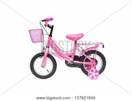 A bicycle for kid in pink color. A pink bike with training wheels on isolated background