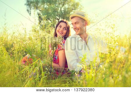 Happy Young Couple enjoying nature outdoors. Beautiful Girlfriend with her boyfriend sitting on summer field with bunch of wildflowers and smiling. Joyful people, vacation concept.