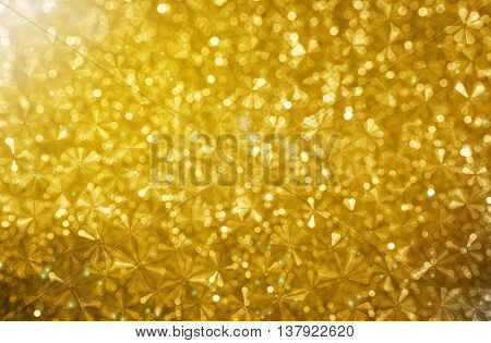 Abstract Small Flower Shape In Golden Glitter Bokeh Background