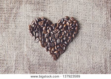 Burlap texture with coffee beans heart shape background, love symbol. Sack cloth canvas with copy space. Seeds at hessian textile