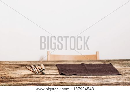 Craftsman workplace, white background, free space. Front view on wooden table with pottery or sculptor tools and chair, copyspace for advertising or text