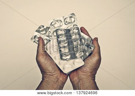 Patient's hand holding a collection of used drug tablets covers - Drug overuse - drug abuse concept