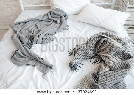 Unmade messy bed with wrinkled sheets and blankets. Top view on bed in the morning after awakening. Unmade bed with white pillows and gray blankets on it, free space