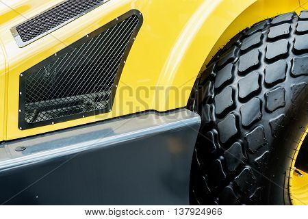 yellow tractor with a big wheel. Wheel with a large tread. focus on the big wheel