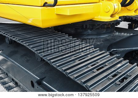 gray tracks on a yellow excavator. focus on excavator tracks