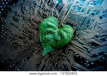 A green leaf with a heart shape on a computer circuit board / green it / green computing / csr / it ethics