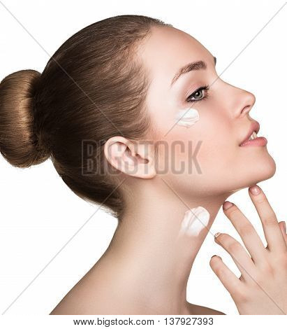 Beautiful model applying cosmetic cream on her face isolated on white