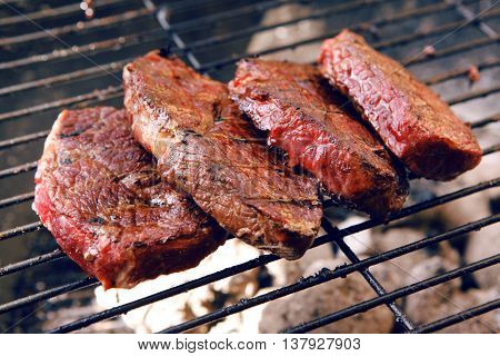 fresh raw beef fillet steak red meat on big round barbecue brazier black grid full burned charcoal