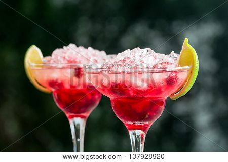 margarita cocktail with lime and raspberries on nature background
