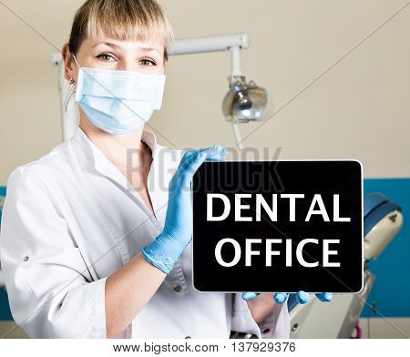 technology, internet and networking in medicine concept - femail dentist holding a tablet pc with dental office sign. at the dental equipment background.