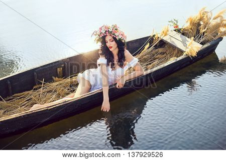 Young sexy woman on boat at sunset. The girl has a flower wreath on her head, relaxing and seiling on river. Fantasy art photography. Concept of female beauty, rest in the nature, and travel by water
