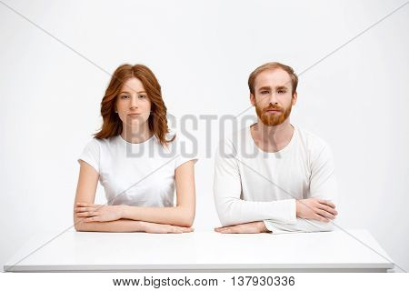 Beautiful redhead girl and boy sitting at the white table. Isolated at the white background. Looking at the camera.