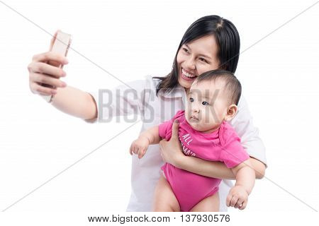 Funny baby girl looking at the camera and smiling make selfie on mobile phone.