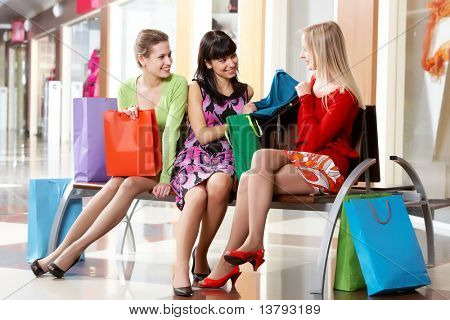 Três meninas sentar-se no centro comercial e mostrando novas roupas