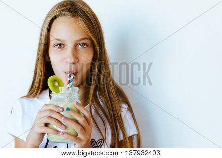 Beautiful teenage girl drinking smoothie shake against white wall