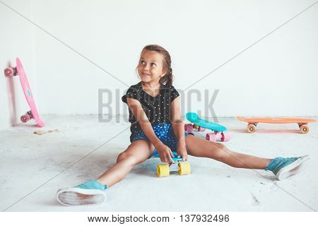 7 years old child wearing cool fashion jeans clothing posing with colorful skateboard in white studio, urban style