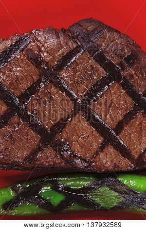 red theme lunch : fresh grilled bbq roast beef steak on red plate with green chili pepper served