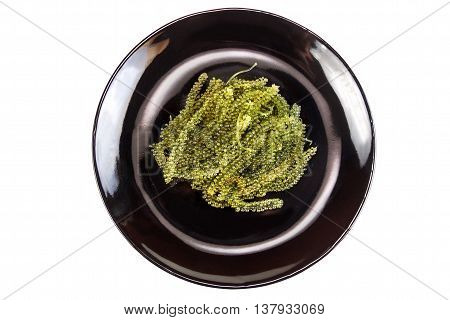 sea grapes or green caviar on a black dish. Isolated on white objects with clipping paths
