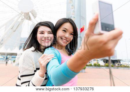 Woman taking selfie by camera in Hong Kong