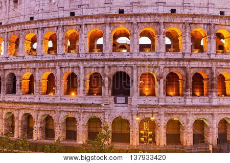 view of Colosseum facade close up illuminated at night in Rome, Italy