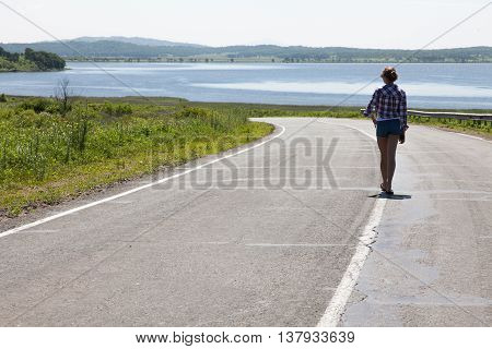 Lonely girl walking along the middle of the road on the background of the sea and the rural landscape.